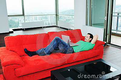 Man relaxing on sofa and work on laptop computer