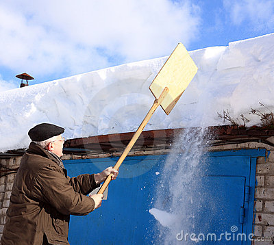 Man removing snow from a roof with a shovel