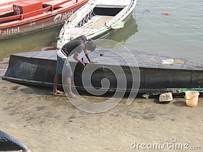 Man repairing boat Assi Ghat Varanasi India