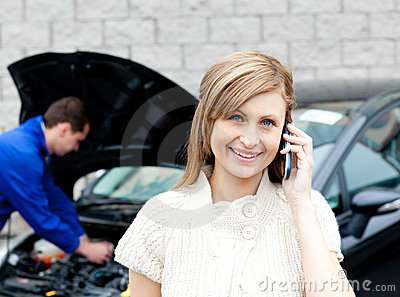 Man repairing car of phoning woman
