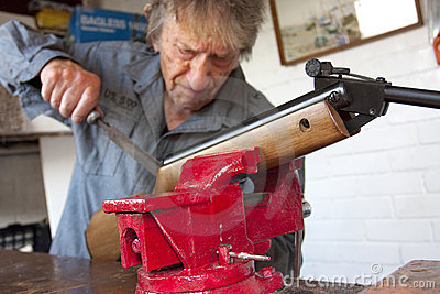 Man repairing a gun in his workshop