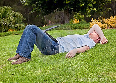 Man resting on lawn with half closed laptop