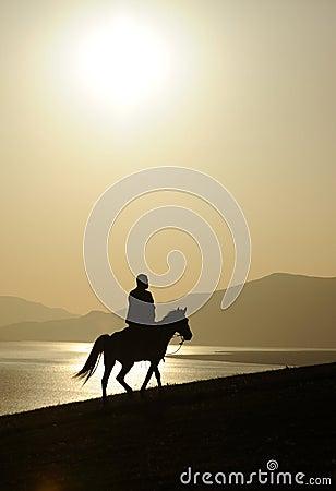 Man ridig horse at sunrise