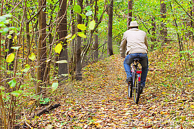 Man is riding a bike in autumn forest