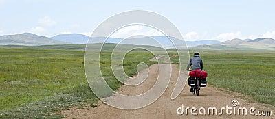 Man Riding Bike through Mongolian Steppes