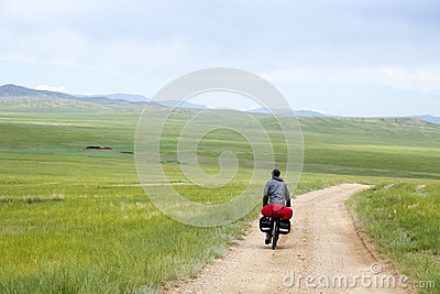 Man Riding Bike through Mongolian Steppes