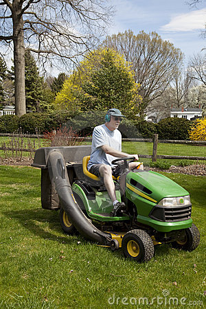 Man on Riding Lawn Mower Editorial Photo