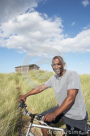 Man Riding Mountain Bike By Dunes