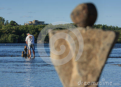 Man in River Balancing Stones Editorial Stock Photo