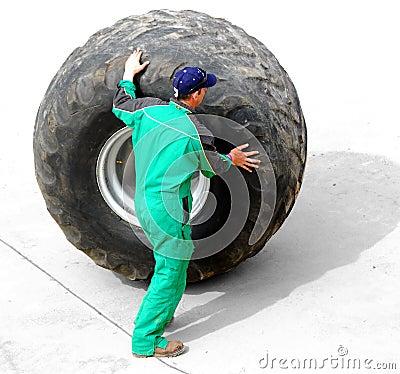 Man rolling huge truck wheel