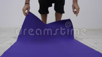 Man rolls apart yoga mat in fitness studio. Freedom, health and yoga concept. Close up slowmotion shot.  stock footage