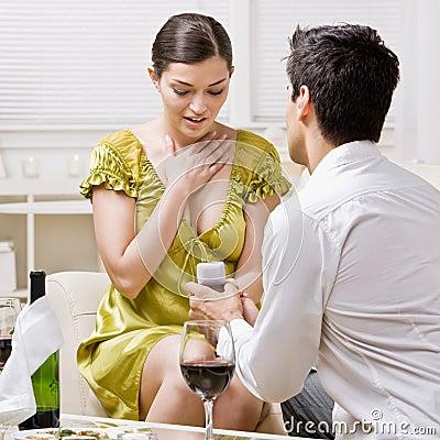 Man romantically proposing to surprised girlfriend