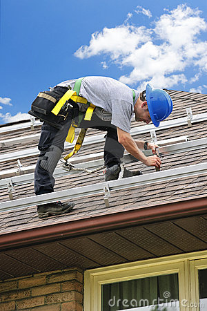 Man on roof installing rails for solar panels