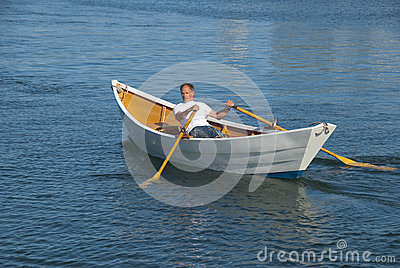 Man rowing a boat in harbor