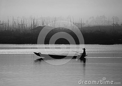 A man rowing boat in a misty lake