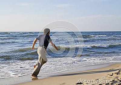 Man running along seashore