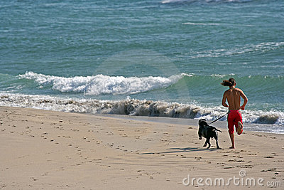 Man running with dog in the beach