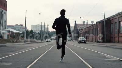 Man running in the middle of the street. Background shot. Slow motion. Abstract concept of individual success and fame. Man running in the middle of the street stock video footage