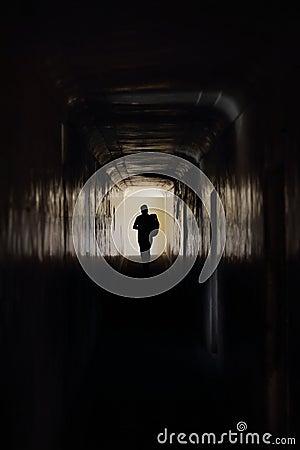 Man runs along a dark corridor