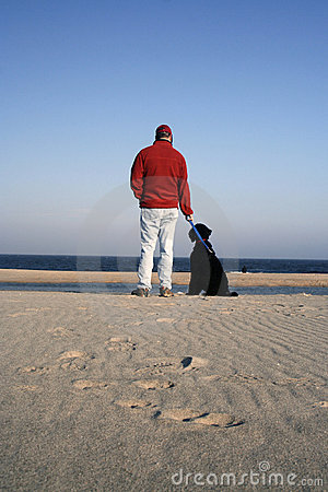 Man on Beach with His Dog Beside Him