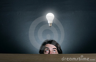 Man s face looking at the  light bulb.