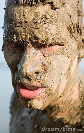 Man s face is very dirty in the mud