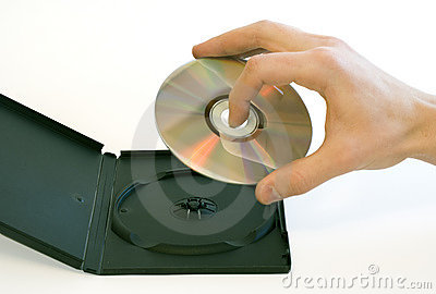 Man s hand holding a compact disc taken from a box