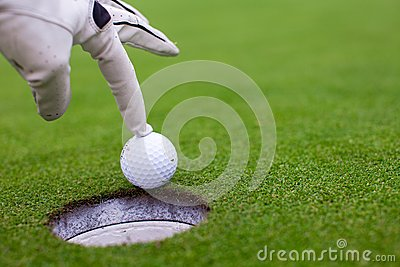 Man s hand putting a golf ball into hole on the