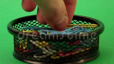 Man's hand takes a paper clip from a black basket against a green background.  stock video footage