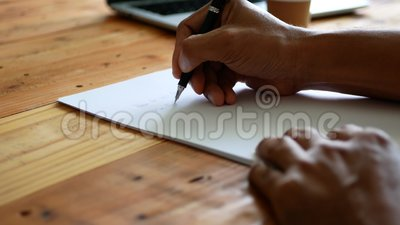 A man`s hand writing on a white paper on a table with a cup of coffee and a computer notebook nearby. Selective focus of a man`s hand writing on a white paper on stock video footage