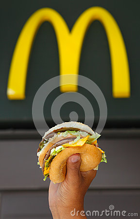 Man s hands, holding onto a burger Editorial Image