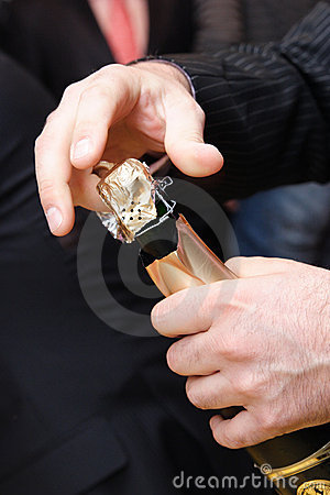 The man s hands opening a bottle of champagne