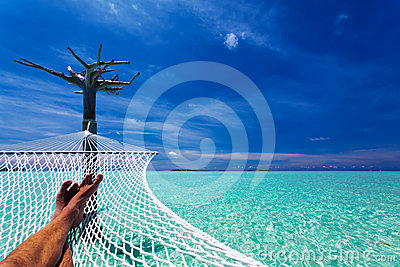 Man s legs in hammock over tropical lagoon