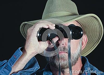 A Man in a Safari Hat Looks Through Binoculars