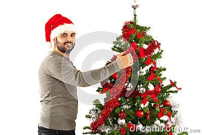 Man with santa hat decorate tree