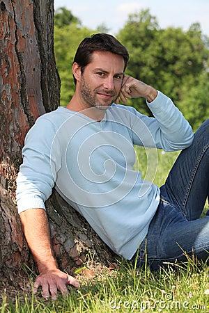 Man sat against tree