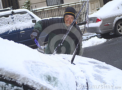 Man scraping snow from windshield