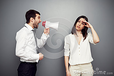 Man screaming at the fatigued woman