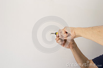 Man screwing a screw with screwdriver at the wall