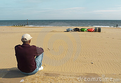 Man seated on sandy beach gazing out to sea