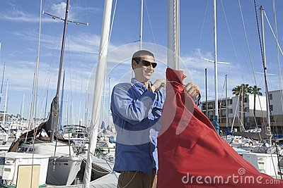 Man Securing Sail Of Boat