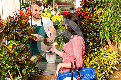 Man selling pot woman customer flower shop