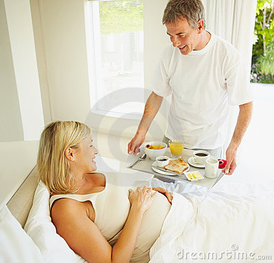 Man serving breakfast to his pregnant wife on bed