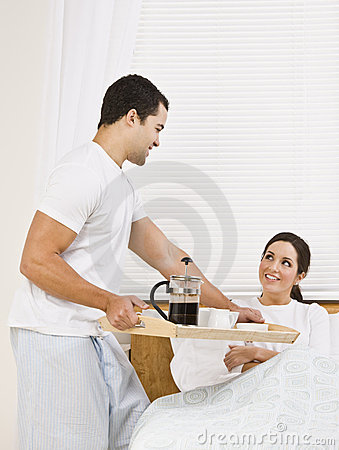 Man Serving Breakfast Tray to Woman
