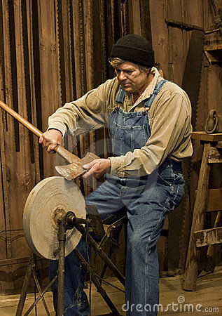 Man sharpening an axe on a grinding stone