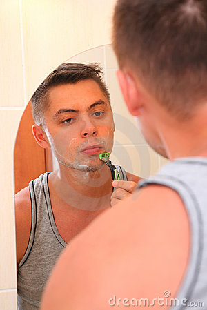 Man shaves against mirror