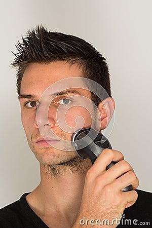 Man shaving beard in face
