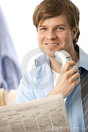 Man shaving with electric razor reading news