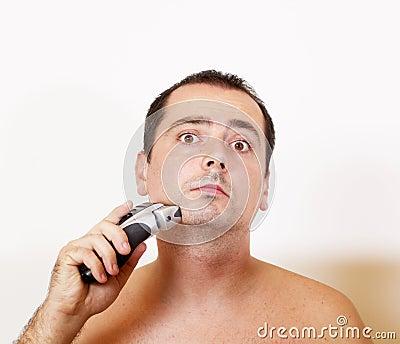Man shaving his beard with an electric razor
