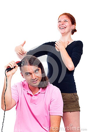Man shaving his hair and woman laughing at him